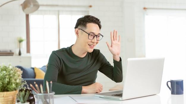 Aziatische zakenman die computerlaptop gebruikt die voor videogesprekconferentievergadering spreekt. werk vanuit huis concept.