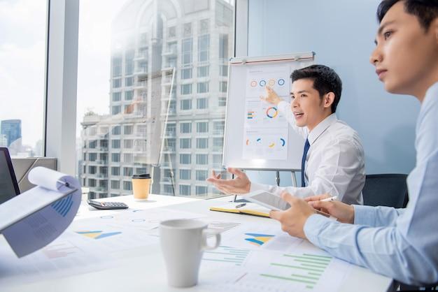 Aziatische zakenman die de grafieken van het businessplan voorstelt