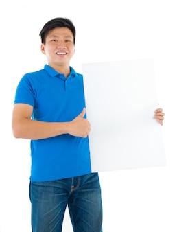 Aziatische zakenman die een lege kaartraad met exemplaarruimte houdt, die zich op duidelijke achtergrond bevindt.