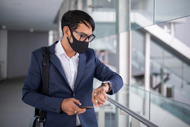 Aziatische zakenman die een masker draagt en op tijd let alvorens in de ochtend te gaan werken.