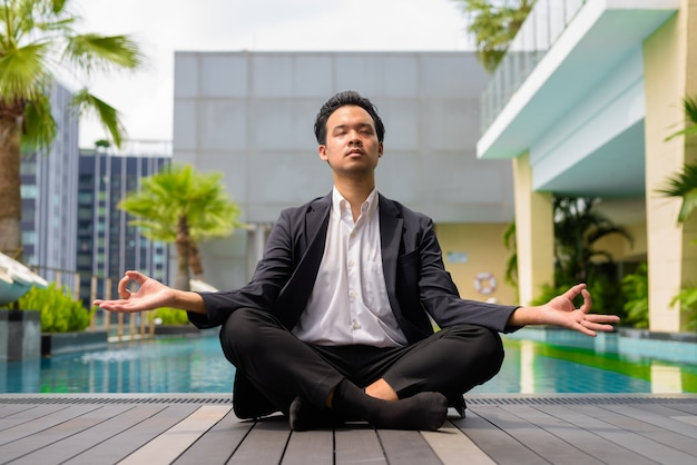 Aziatische zakenman die een pak draagt en yoga en meditatie doet naast het zwembad