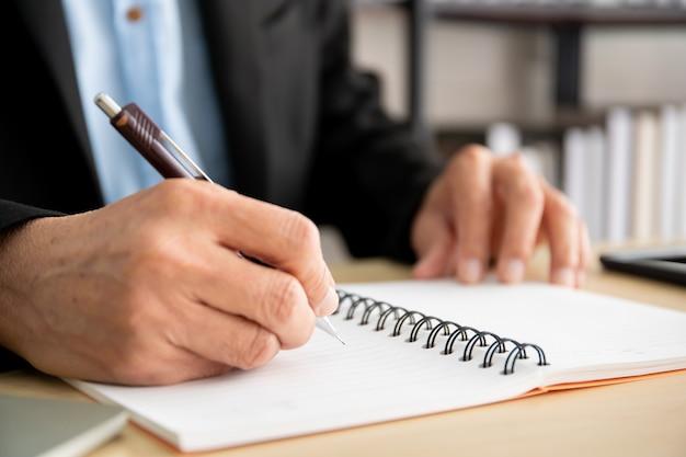 Aziatische zakenman die een potlood gebruikt om op het lege notitieboekje te schrijven.