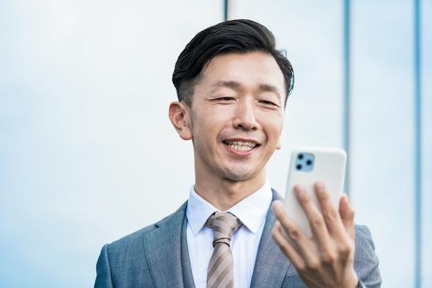 Aziatische zakenman die een smartphonescherm bekijkt