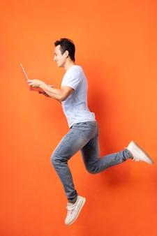 Aziatische zakenman die en laptop springt houdt
