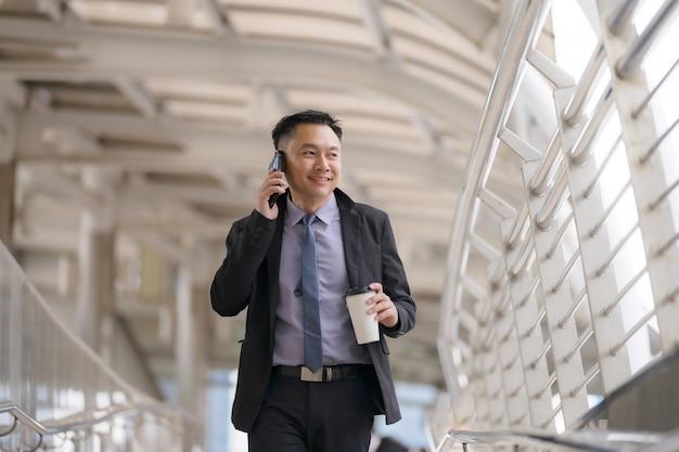 Aziatische zakenman die en op mobiele telefoon loopt spreekt