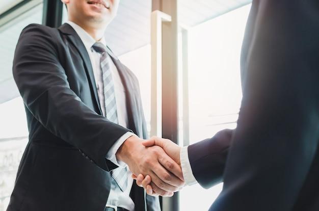 Aziatische zakenman die handdruk met een onderneemster maakt - groet en handeldieconcepten