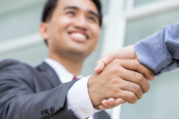 Aziatische zakenman die handdruk met het glimlachen gezicht maakt