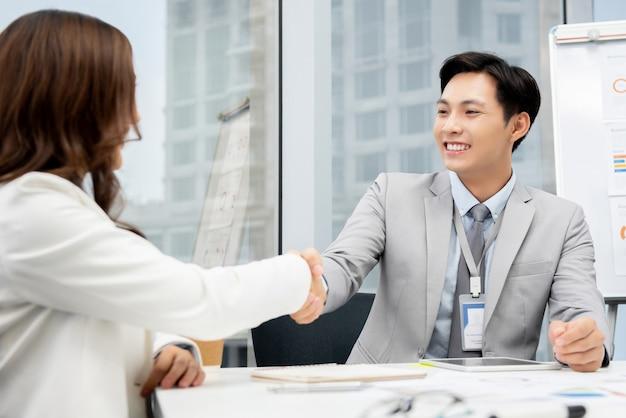 Aziatische zakenman die handdruk met onderneemster in bureau maken