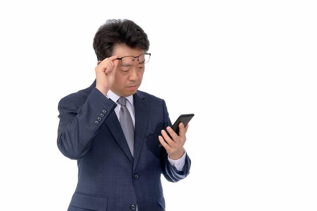 Aziatische zakenman die iets op zijn mobiele telefoon probeert te lezen. slecht zicht, presbyopie, bijziendheid.