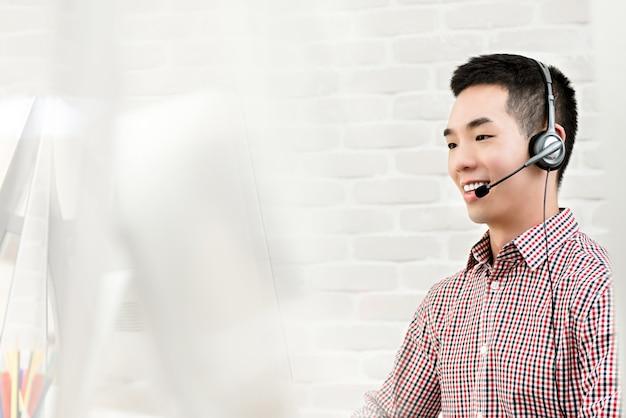 Aziatische zakenman die in call centre als agent van de telemarketerdienst werkt