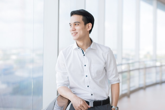 Aziatische zakenman die jong wegkijkt, dus geluk in gezelschap velt