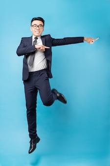 Aziatische zakenman die kostuum draagt en op blauwe muur springt