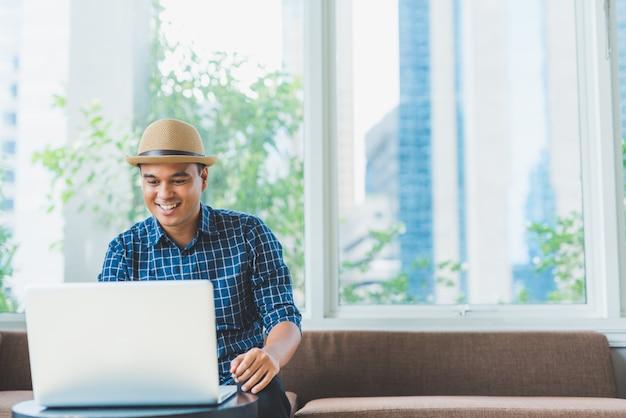 Aziatische zakenman die laptop computernotitieboekje voor het werk gebruiken.