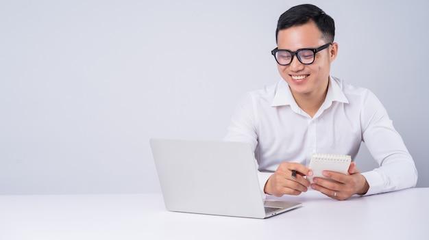 Aziatische zakenman die laptop op wit met behulp van