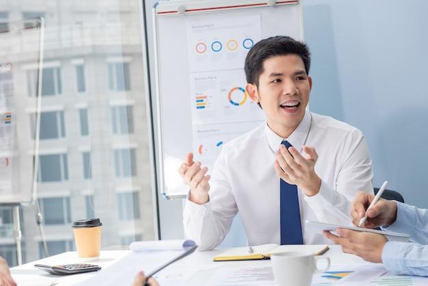 Aziatische zakenman die met collega op de vergadering in bureau spreekt