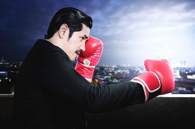 Aziatische zakenman die met rode bokshandschoenen met stadsgezichtenachtergrond vecht