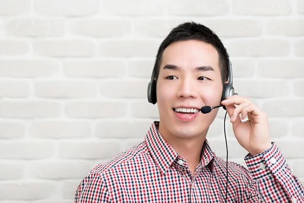 Aziatische zakenman die microfoonhoofdtelefoon dragen als telemarketing de agent van de klantendienst, het concept van de call centrebaan