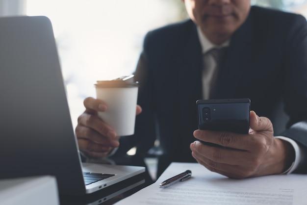 Aziatische zakenman die mobiele telefoon gebruikt en koffie drinkt die op kantoor werkt