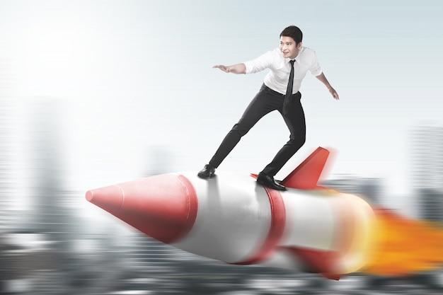Aziatische zakenman die op een raket vliegt