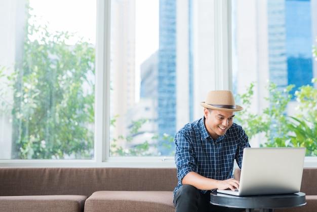 Aziatische zakenman die op laptop kijkt terwijl het zitten op bank.