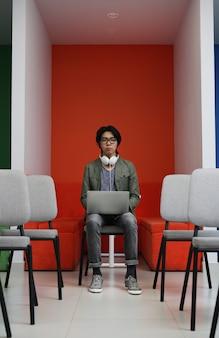 Aziatische zakenman die op laptop werkt