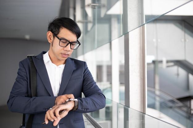 Aziatische zakenman die op tijd let en in de ochtend gaat werken.