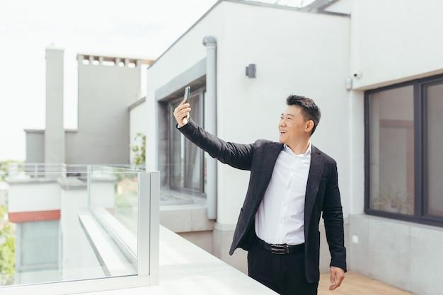 Aziatische zakenman die op videotelefoon spreekt die zich op balkonterras bevindt