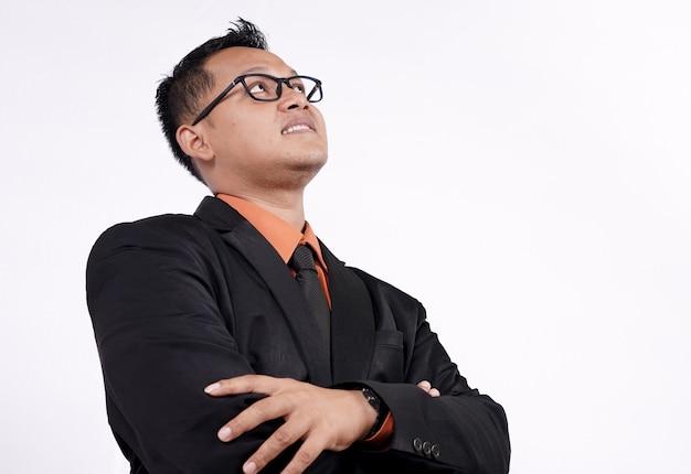 Aziatische zakenman die op witte achtergrond denkt