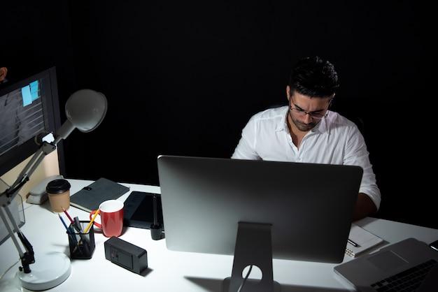 Aziatische zakenman die over tijd laat bij nacht blijven die in het bureau werken
