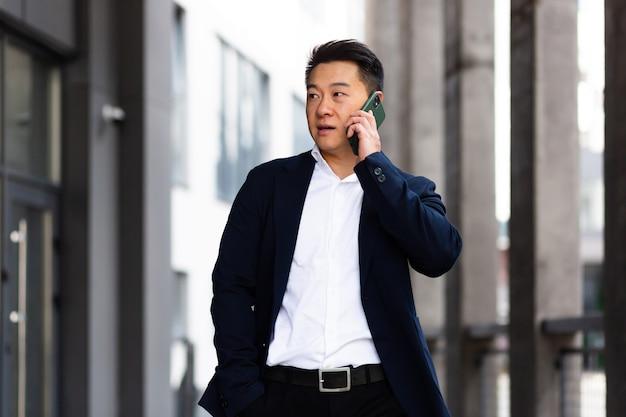 Aziatische zakenman die serieus aan de telefoon praat, heeft een boos gesprek