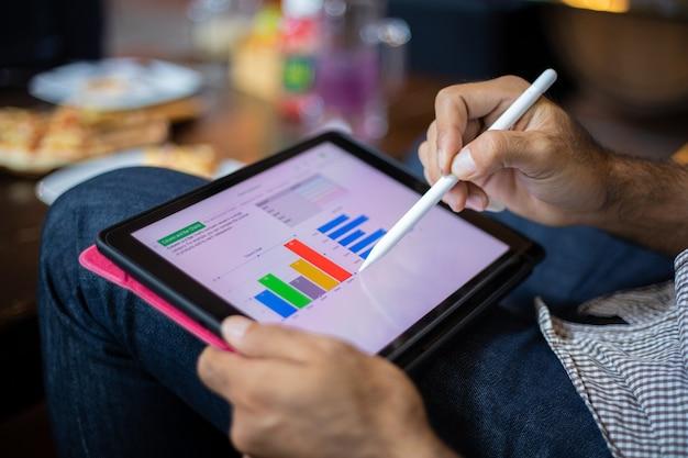 Aziatische zakenman die tablet gebruikt om in coffeeshop te werken
