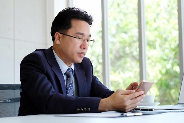 Aziatische zakenman die telefoon met behulp van terwijl het werken op kantoor, ceo bedrijfs aziatische mens met slimme telefoon voor communicatie terwijl het zitten in bureau, mensenzaken en technologie