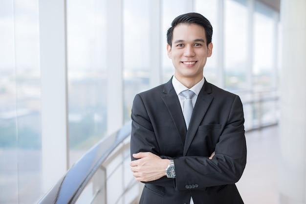 Aziatische zakenman die zelfverzekerd glimlacht terwijl hij alleen staat in een helder modern kantoor