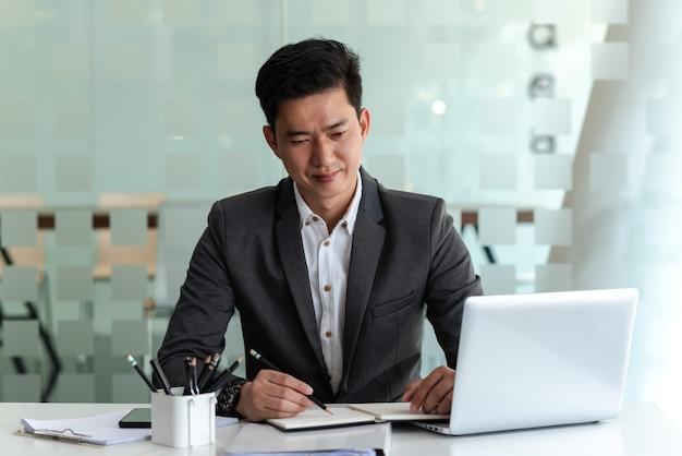 Aziatische zakenman draagt een pak om op kantoor aantekeningen te maken en een laptop.