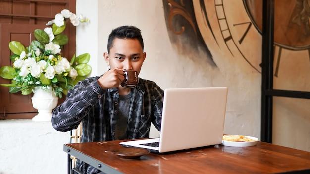 Aziatische zakenman drinken koffie werken met laptop in café