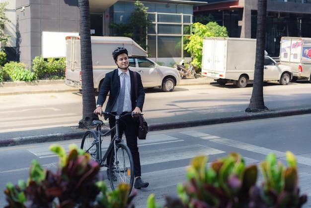 Aziatische zakenman duwt een fiets over een oversteekplaats op een stadsstraat tijdens een ochtend pendelen