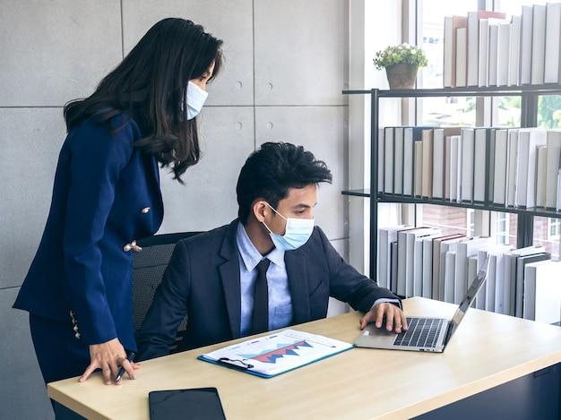 Aziatische zakenman en vrouw die kostuum en beschermende gezichtsmaskers dragen die computer op bureau met behulp van