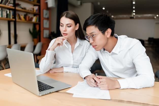 Aziatische zakenman en vrouwenmedewerker die aan laptop en documenten samenwerken