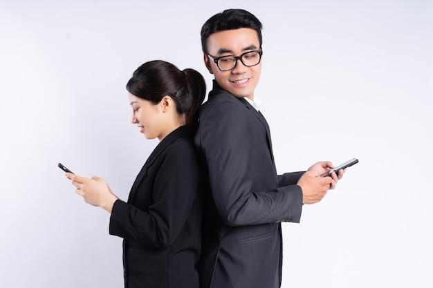 Aziatische zakenman en zakenvrouw die smartphone op witte achtergrond gebruiken