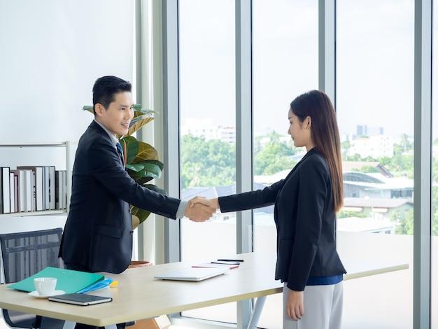 Aziatische zakenman en zakenvrouw handen schudden in kantoor