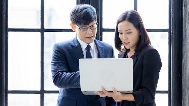 Aziatische zakenman en zakenvrouw opstarten met behulp van computerlaptop samen terwijl ze in kantoorgebouwramen staan, succesvolle jonge zakenpartners in pakken die naar laptop strategische analyse kijken.