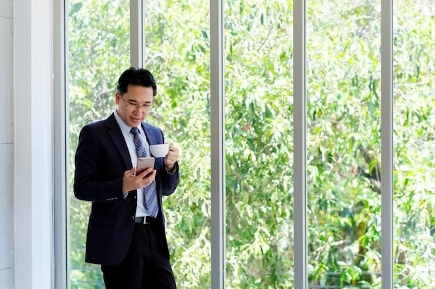 Aziatische zakenman gebruikend slimme telefoon en drinkend koffie op kantoor, het bureauleven en bedrijfsconcept