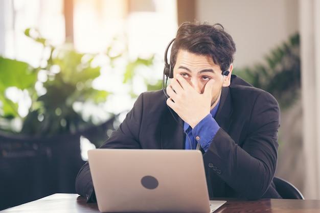 Aziatische zakenman heeft actie met een vermoeide uitdrukking tussen het gebruik van computerlaptop. hij bedekt zijn gezicht met een hand die van streek is door zijn werk.