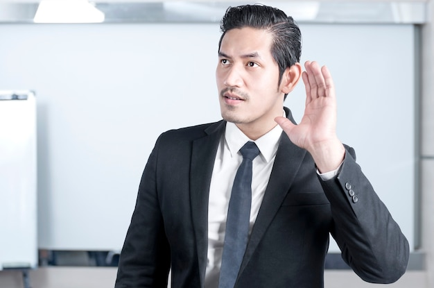 Aziatische zakenman hoort iets op de kantoorruimte