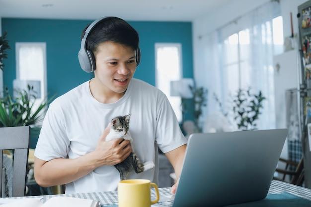 Aziatische zakenman in gesprek met collega-team in videogesprekconferentie met kitten en glimlachgezicht. man met behulp van computer laptop en hoofdtelefoon voor online vergadering. slim werken vanuit huis concept.