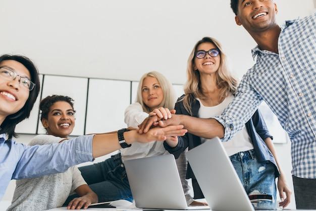 Aziatische zakenman in lederen polshorloge hand in hand met partners en glimlachen. indoor portret van team van kantoorpersoneel met plezier voor groot project.