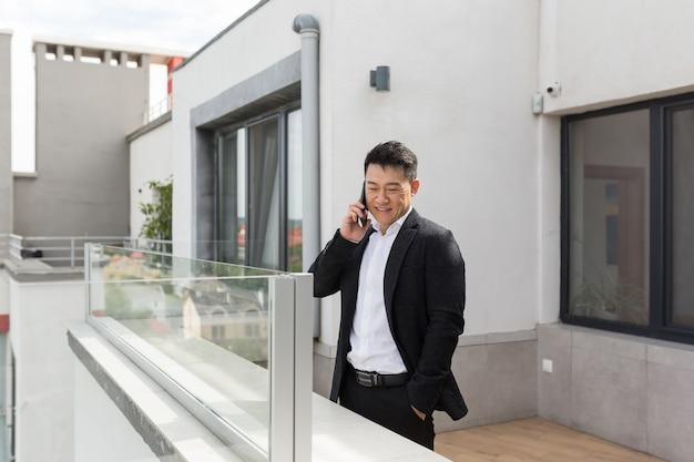 Aziatische zakenman in pak geniet van de telefoon die op het moderne kantoorcentrum staat succesvol