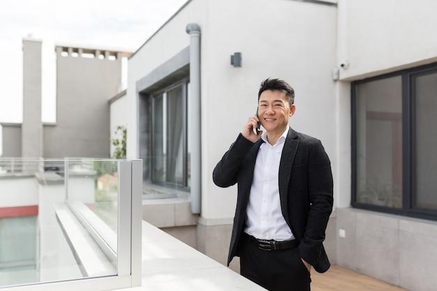 Aziatische zakenman in pak geniet van het telefoonterras van een succesvol kantoorcentrum