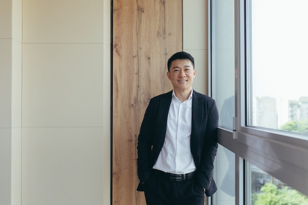 Aziatische zakenman in pak kijkend naar camera bij het raam van een modern kantoorcentrum modern