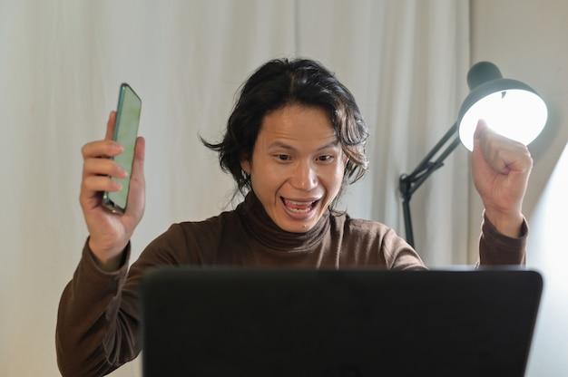 Aziatische zakenman kijkt erg verbaasd naar zijn laptop